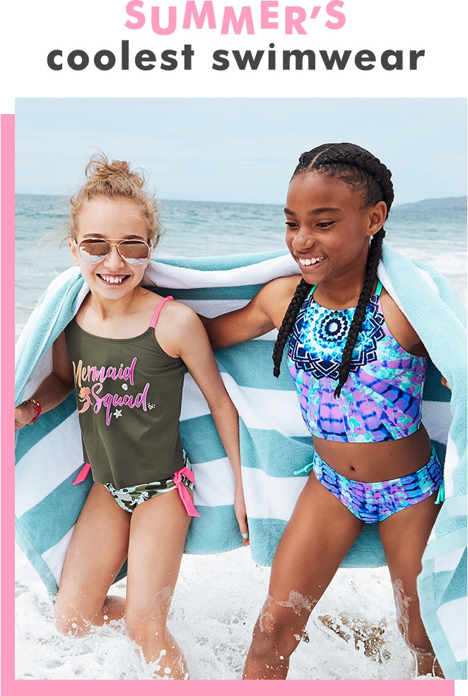 Girls walking in the ocean wearing mermaid print and geometric print swimsuits from Justice