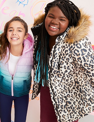 Two smiling girls wearing an ombre puffer and a cheetah print puffer from Justice